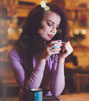Beautiful woman enjoying aromatic coffee